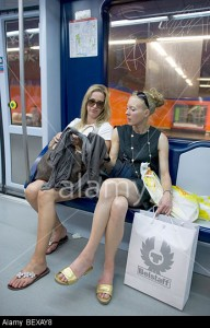 Two Trendy Women travelling on the Subway in Madrid with shopping bags after a day's shopping.